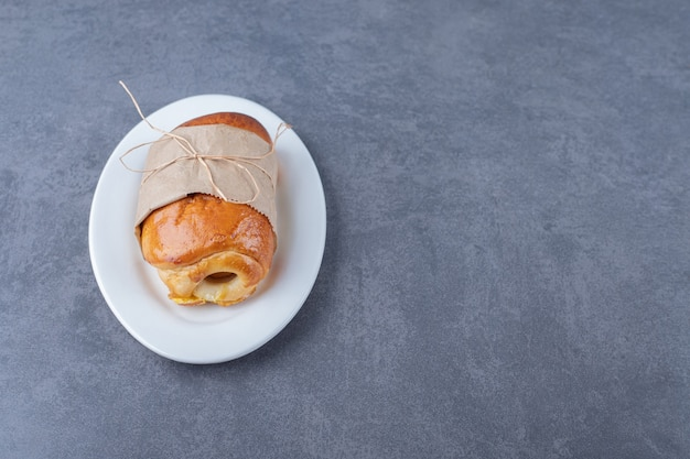 Pagnotta dolce avvolta in carta sul piatto, sul marmo.