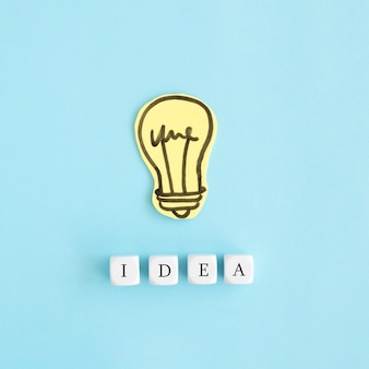 Paper yellow bulb with white ideas blocks over blue colored background