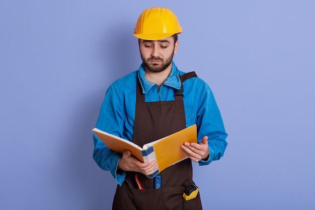 Внутреннее изображение расстроенного неудовлетворенного опытного инженера представляя изолированный над голубой стеной в студии, держащ желтый papercase, просматривая проекты, нахмурив выражение лица.