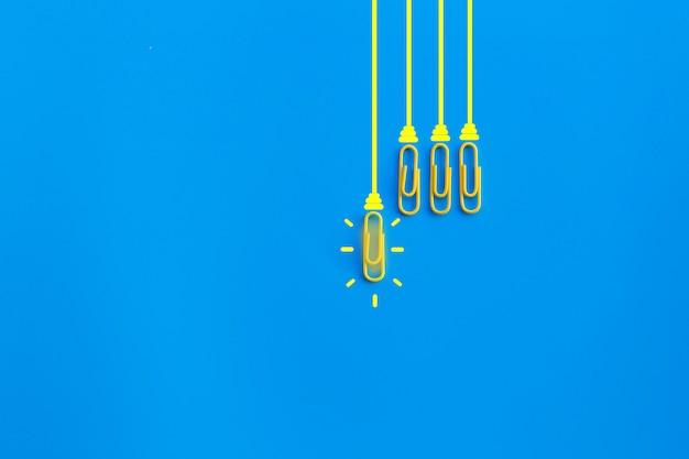 Концепция отличных идей с paperclip, думая, творческими способностями, электрической лампочкой на голубой предпосылке, новой концепцией идей.