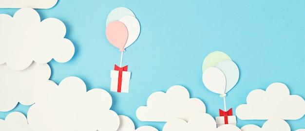 Papercut 풍선과 구름과 푸른 하늘에 떠있는 선물 상자