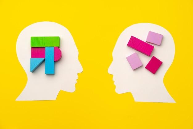 Papercut силуэт головы с игрушечными конструкторами на желтом фоне