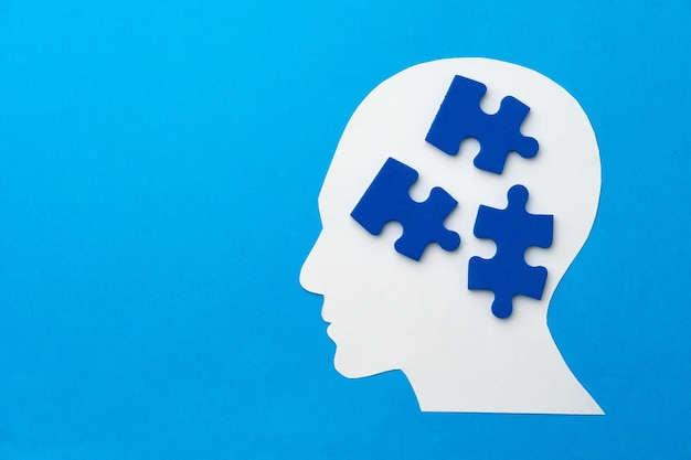 Papercut head with jigsaw puzzle pieces