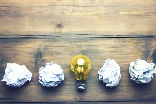 木製のテーブルの上の紙と電球