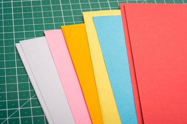 Papers for art of different size on green cutting mat