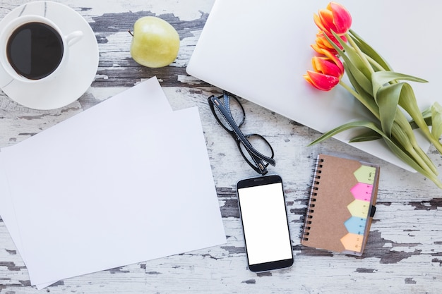 Papers and coffee cup near smartphone on desk with tulip flowers