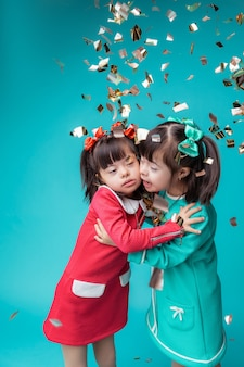 紙が落ちる。カラフルなドレスを着たかなり若い姉妹が、紙吹雪で覆われている間、お互いを抱きしめています