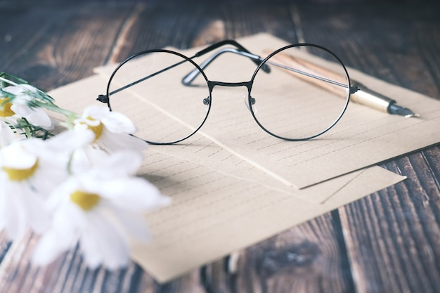 Papers  flower eyeglass and a fountain pen on wooden table