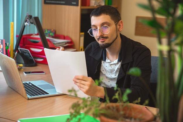 Оформление документации. кавказский предприниматель, бизнесмен, менеджер, работающий в офисе. выглядит серьезно и занятой в классической одежде. понятие работы, финансов, бизнеса, успеха, лидерства.