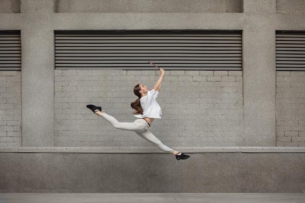 서류. 점프 높이에서 실행에 도시 건물 벽 앞 점프 젊은 여자.