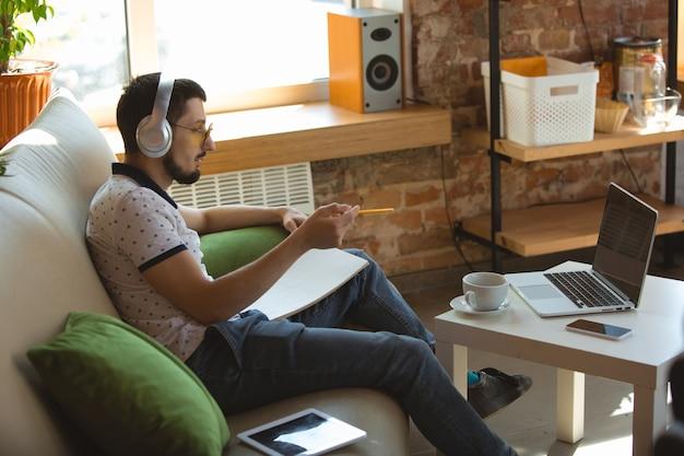 事務処理。コロナウイルスまたはcovid-19検疫、リモートオフィスの概念の間に在宅勤務の男性。スマートフォンやコンピューターで仕事をしているマネージャーの青年実業家がオンライン会議を開いています。