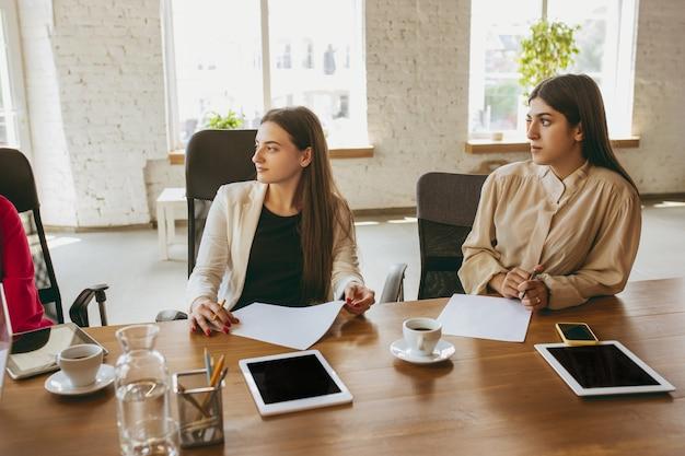 Оформление документации. молодая деловая женщина в современном офисе с командой. творческая встреча, постановка задач. женщины во фронт-офисе работают. понятие финансов, бизнеса, женской силы, включения, разнообразия, феминизма.