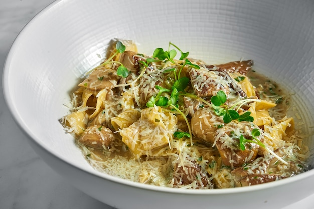 Pappardelle pasta with white forest mushrooms, mushroom sauce, grated parmesan and microgrine in a white bowl on white marble