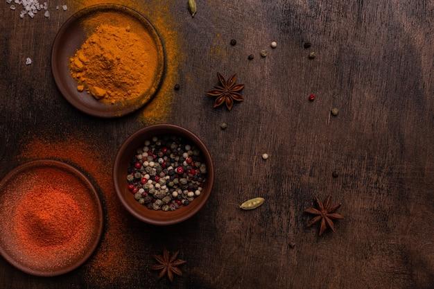 Паприка, перец, кардамон, соль и куркума на деревянном фоне, плоская планировка