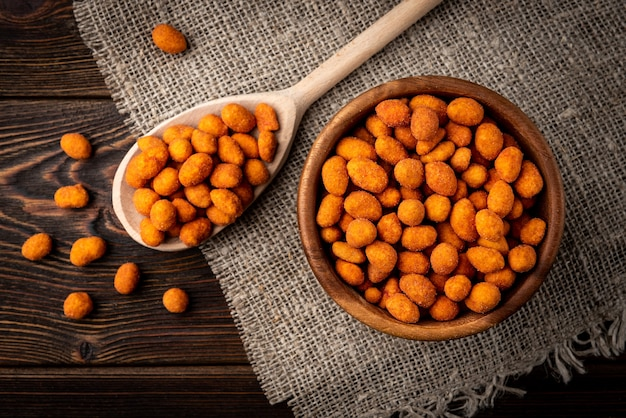 Арахис жареный паприкой на темном деревянном фоне. вкусная закуска из арахиса.