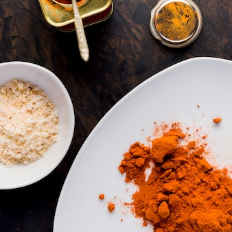 Paprika on white plate, salt and a pot on golden background