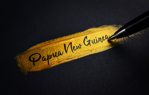 Papua new guinea handwriting text on golden paint brush stroke