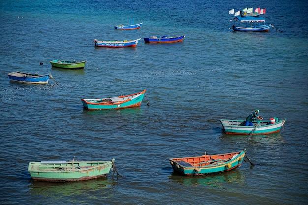 Паракас, перу, 3 июля 2019 г. взрослый мужчина в рыбацкой лодке, вокруг небольших рыбацких лодок в море.