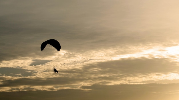 Parachute or paramotor fly in sunset,black shadow, sport activity