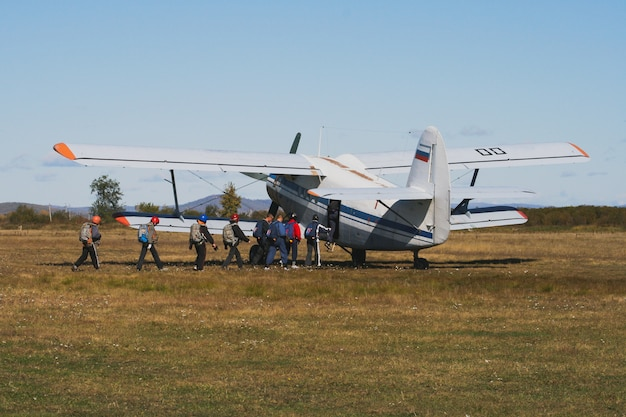 Parachutists enter the biplane plane before the jump, plane in the field before takeoff in the summer.