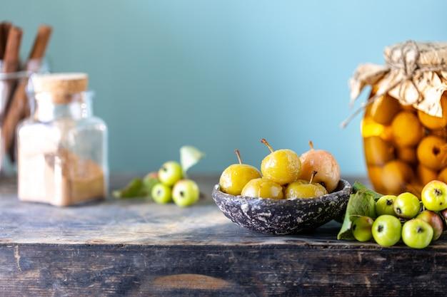 Варенье из райских яблок и райские яблоки в сахарном сиропе на старой деревянной поверхности