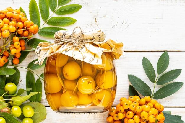 白い木製のテーブルに砂糖シロップの楽園りんご。秋の収穫。パラダイスアップルジャム。上面図