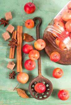 Райские яблоки, на деревянном столе в деревенском стиле, железная кружка.