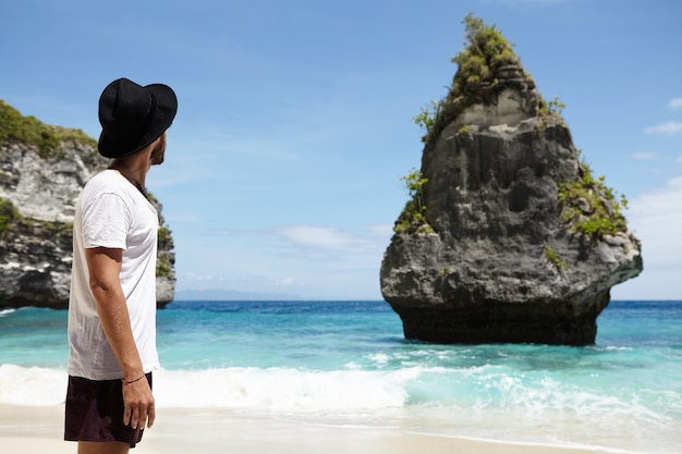 Paradise on earth. unrecognizable caucasian man in black headwear enjoying ideal place at ocean shore with rocky cliffs and turquoise water that he found during his long trip along coastline
