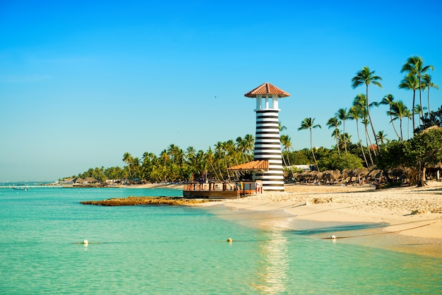 Райский тропический остров в доминиканской республике. белый песок, синее море, чистое небо и маяк на берегу