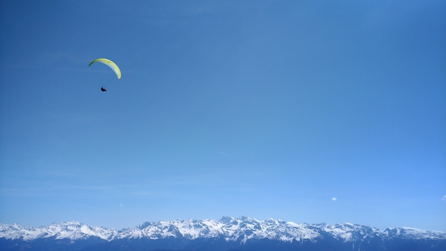 Paraglider in the blue sky of mountains