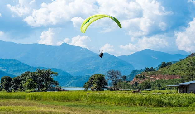 Paraglider flies over a meadow, pokhara, nepal