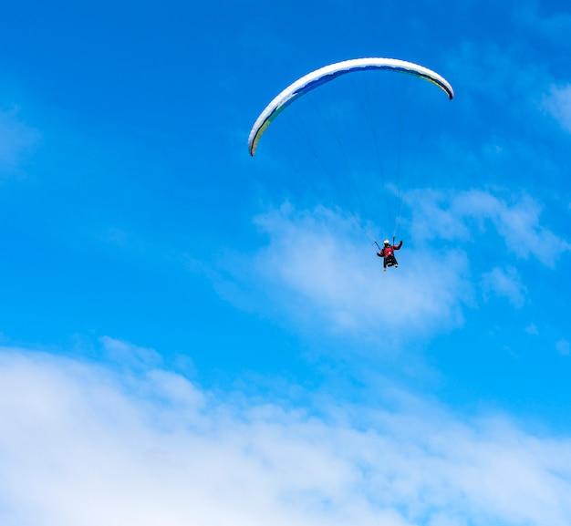 Paraglider flies paraglider in the sky.