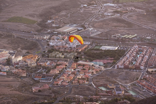 Paraglider flying over adeje village in south tenerife island, canary islands, spain.