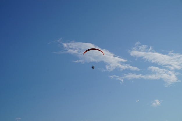 Paraglider flying against the blue sky, extreme sports.