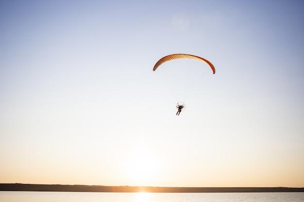 日没で飛んでいるパラグライダー