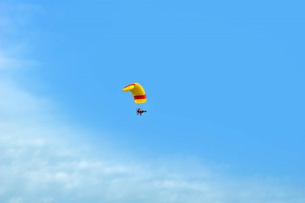Paraglider flying in blue sky.