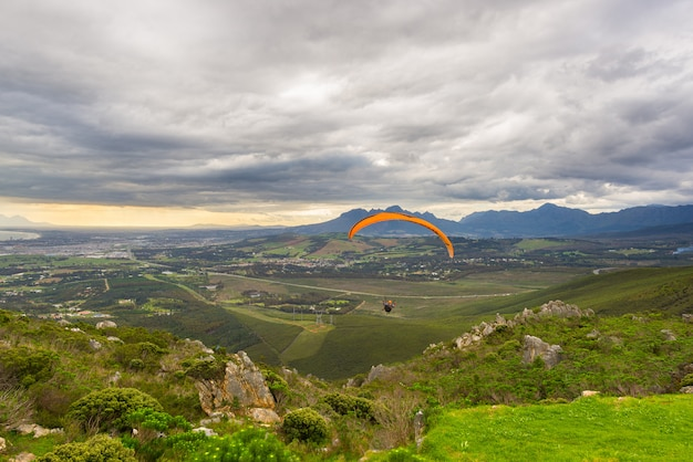 Paraglider flying over the green mountains