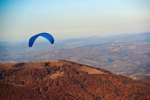 秋の山脈を飛んでいるパラグライダー。