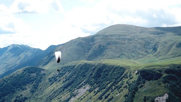 Paraglider flying over mountains during summer day - georgia, kazbegi