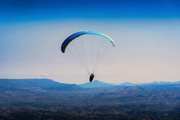 Paraglider flying over mountains in the morning on summer day at north of thailand.