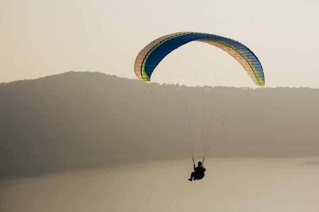 ガンドルフォ湖の上空を飛ぶパラグライダー。