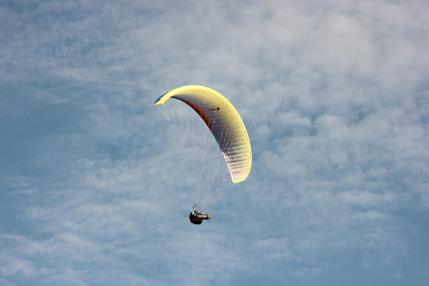 Paraglider flying on a parachute against a blue sky with clouds