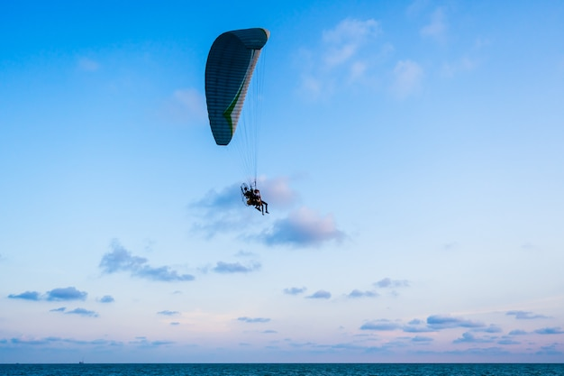 Paraglider flying on sea and sky