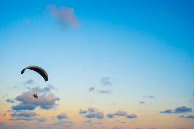 Paraglider flying on sky at sunset