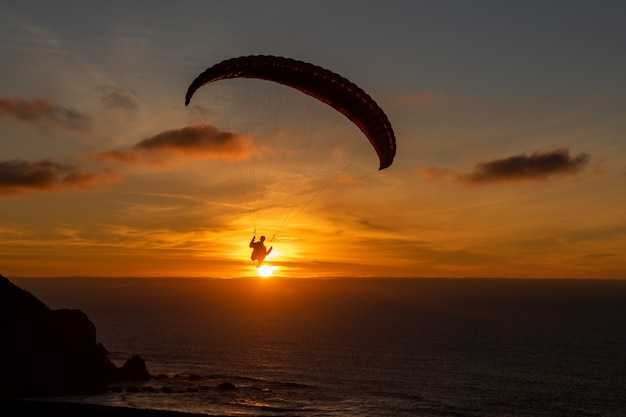 Paraglider flying over thesea shore at sunset. paragliding sport