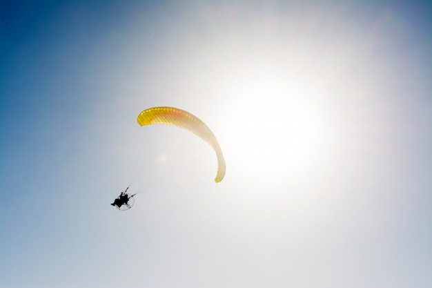 Paraglider flying with paramotor on blue sky