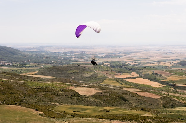 Paraglider silhouette flying over valley in loarre, huesca, spain.