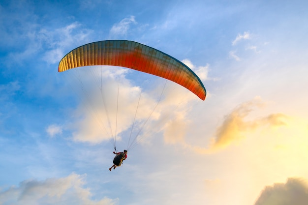 Paraglider soaring in the blue sky