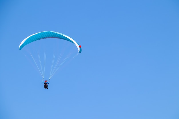 Параплан парит в голубом небе.