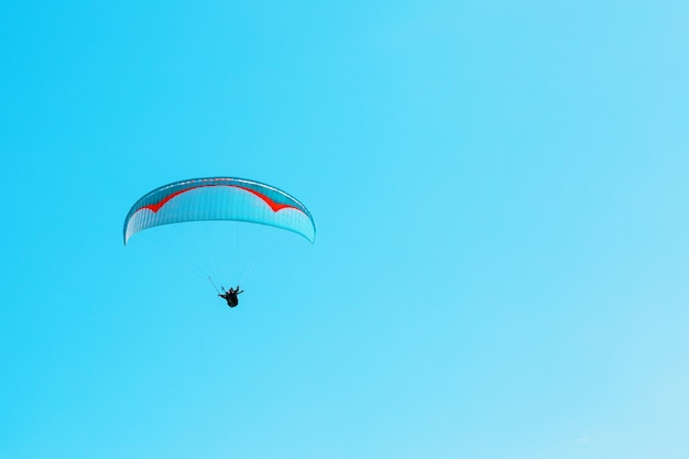 Paraglider soars against the blue sky with clear space